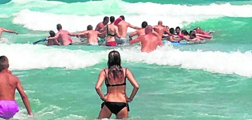 Una cadena humana rescata en La Manga a cuatro bañistas en riesgo de ahogarse