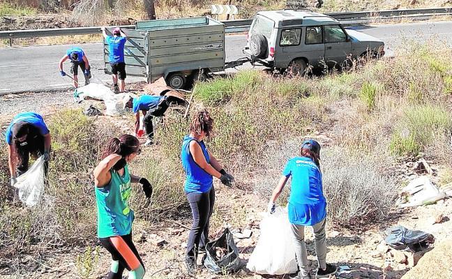 Unos 60 voluntarios retiran basura y plantas invasoras de la rambla del Garruchal