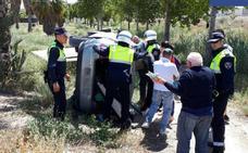 Atrapados al volcar su coche en la mota del río en Murcia