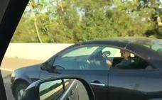 Graban a un conductor tocando la guitarra al volante