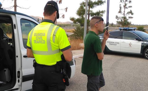 Un agente, junto al camionero detenido.