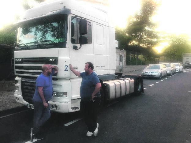 Jesús Antonio López (i) charla con uno de sus empleados, ayer en Tarragona, junto a su camión./LV