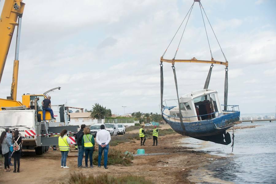 Una grúa retira una embarcación semivarada en el Mar Menor