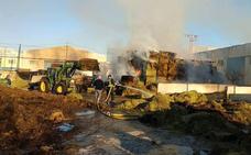 El fuego consume varias pilas de balas de paja en una granja de Santomera