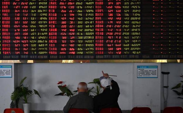 98f8be33f Dos inversores observan un panel informativo en la bolsa de Shanghai.