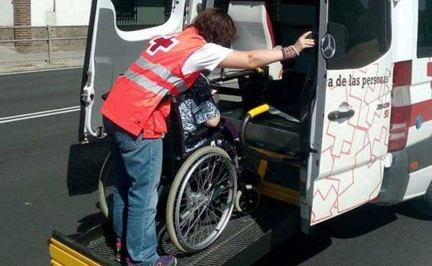 A Red Cross volunteer helps an elderly woman access the adapted vehicle in a file image.