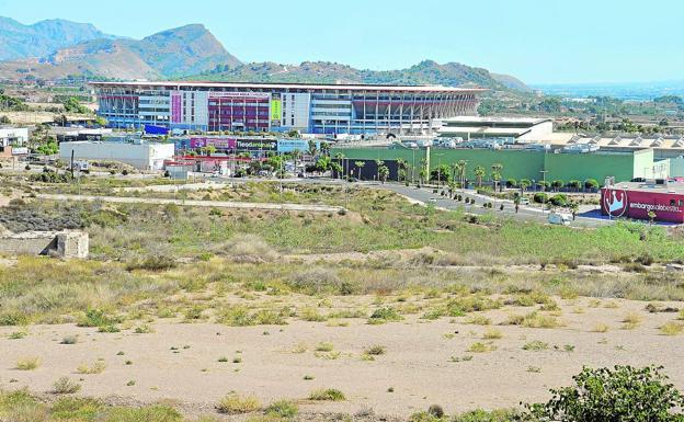 En primer plano, parte de los terrenos donde iría asentada la nueva ciudad deportiva grana. Al fondo, el estadio Enrique Roca.