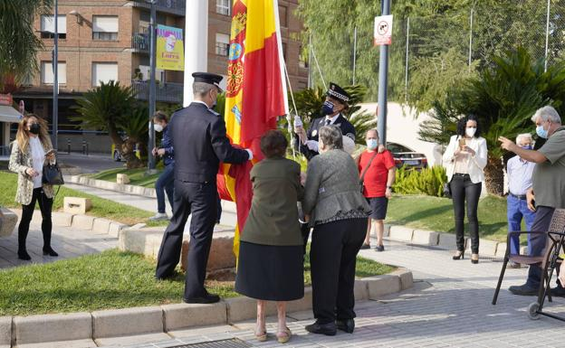 Moment in which two women raise the flag of Spain.